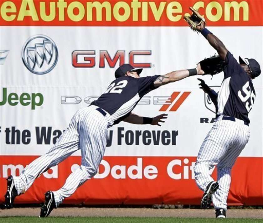 New York Yankees' Slade Heathcott, left, collides with Ronnier Mustelier after Mustelier caught a fly out by Toronto Blue Jays' Edwin Encarnacion during the seventh inning of a spring training exhibition baseball game, Thursday, Feb. 28, 2013, in Tampa, Fla. Toronto won 1-0. (AP Photo/Matt Slocum)