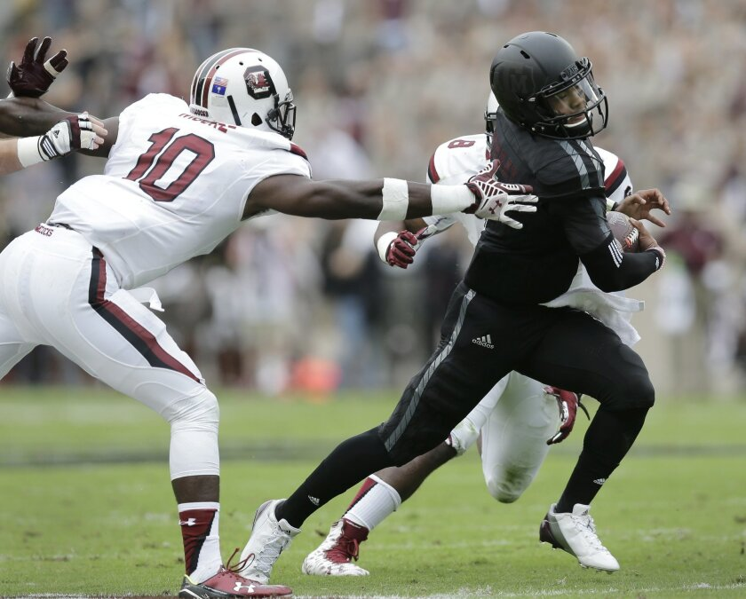 Texas A&M quarterback Kyler Murray, right, looks to escape the grasp of South Carolina linebacker Skai Moore (10 ) during the first half of an NCAA college football game, Saturday, Oct. 31, 2015, in College Station, Texas. (AP Photo/Eric Gay)