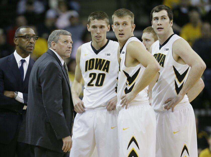 Iowa assistant coach Kirk Speraw, left, huddles with players Jarrod Uthoff (20), Josh Oglesby and Zach McCabe, right, during the first half of an NCAA college basketball game against Northwestern, Thursday, Jan. 9, 2014, in Iowa City, Iowa. Iowa coach Fran McCaffery was suspended for the game after being ejected for berating officials last weekend in a loss at Wisconsin. (AP Photo/Charlie Neibergall)