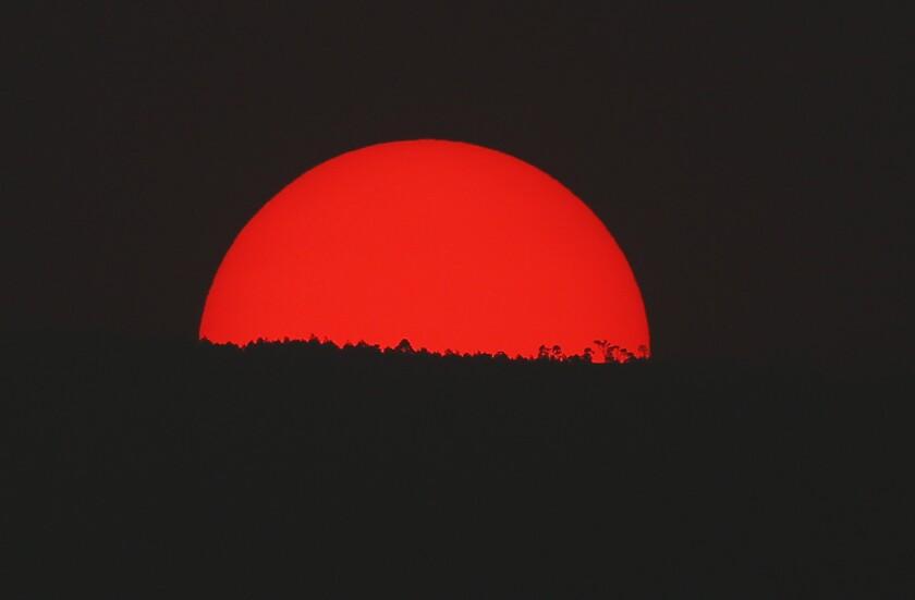 Teñido de rojo por una espesa nube de humo y contaminación, el sol se pone sobre las montañas de la Ciudad de México, el lunes 13 de mayo de 2019. (AP Foto/Marco Ugarte)