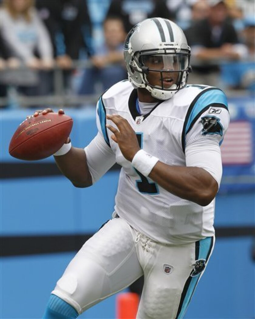 Carolina Panthers' Cam Newton (1) rolls out to pass against the Green Bay Packers during the first quarter of an NFL football game in Charlotte, N.C., Sunday, Sept. 18, 2011. (AP Photo/Chuck Burton)