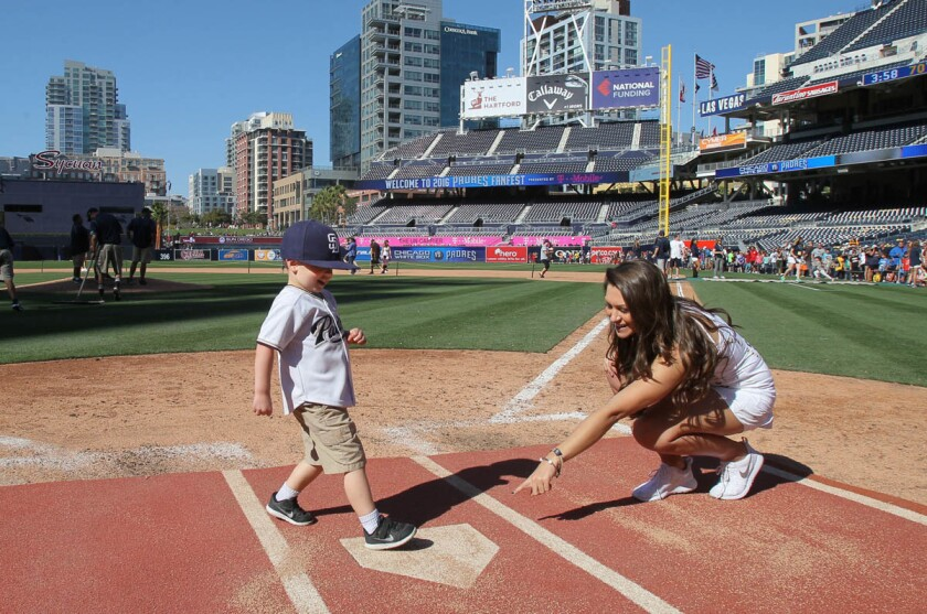 Gauge Perez, 3, of San Diego, gets directed by a Pad Squad member to tag home plate as he and hundreds of other fans ran the bases after the Padres exhibition game against the White Sox.