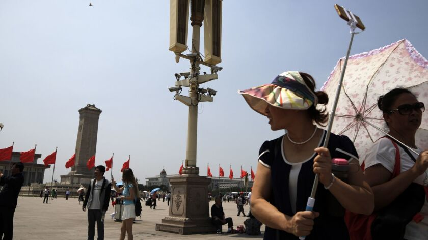 Tourists gather near a pole attached with security cameras to monitor Tiananmen Square in Beijing, T