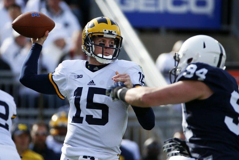 Michigan quarterback Jake Rudock (15) passes under pressure by Penn State defensive end Evan Schwan (94) during the first half of an NCAA college football game in State College, Pa., Saturday, Nov. 21, 2015. (AP Photo/Gene J. Puskar)