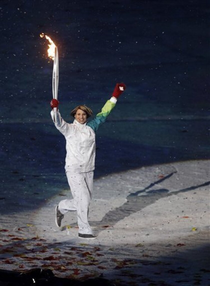 Catriona Le May Doan carries the Olympic torch during the opening ceremony for the Vancouver 2010 Olympics in Vancouver, British Columbia, Friday, Feb. 12, 2010. (AP Photo/Julie Jacobson)