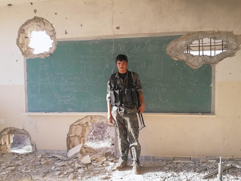 YPG militia member Zinar Kochar, 21, stands in a destroyed school in Jazaa, Syria. The blackboard still bears a math lesson.