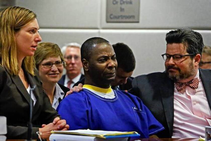 Kash Delano Register begins to cry as he realizes he will be a free man; with him are his lawyers, Lara Bazelon, left, Laurie Levenson, second from left, and Adam Grant, right, with the Loyola School of Law.
