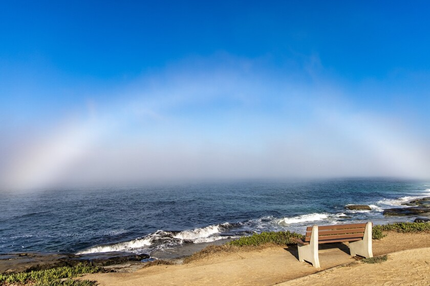 "A fog bow, or ""ghost rainbow,"" appears at Windansea, a result of very small water droplets in fog."
