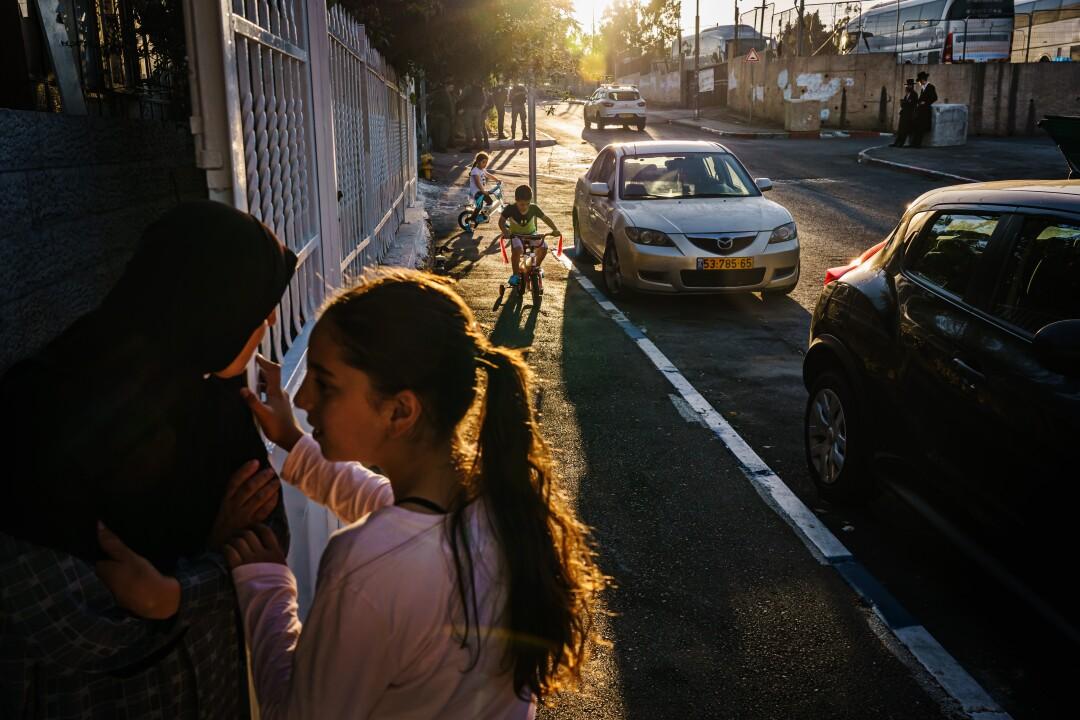 The evening sun casts long shadows a street as children play.