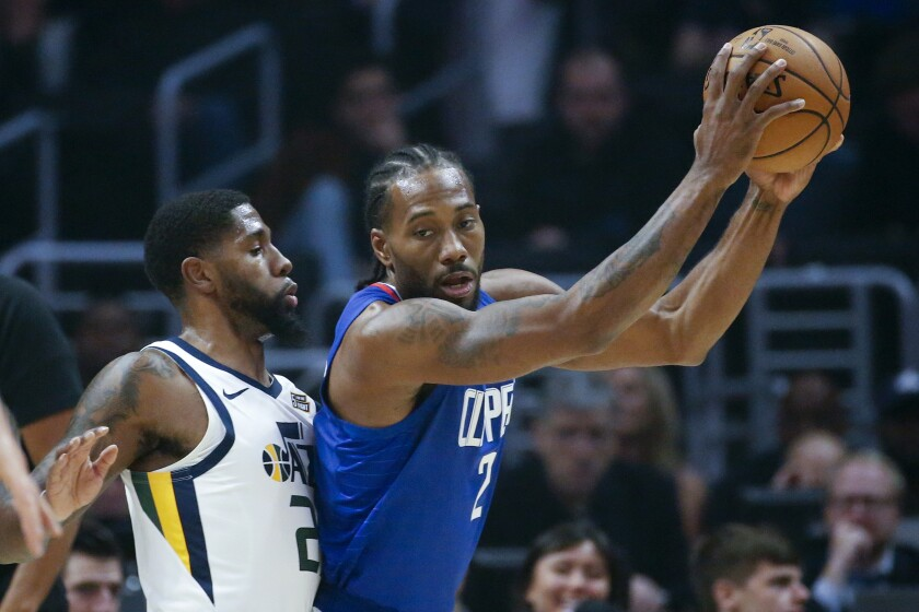 Los Angeles Clippers' Kawhi Leonard (2) is defended by Utah Jazz's Royce O'Neale (23) during the first half of an NBA basketball game Sunday, Nov. 3, 2019, in Los Angeles. (AP Photo/Ringo H.W. Chiu)