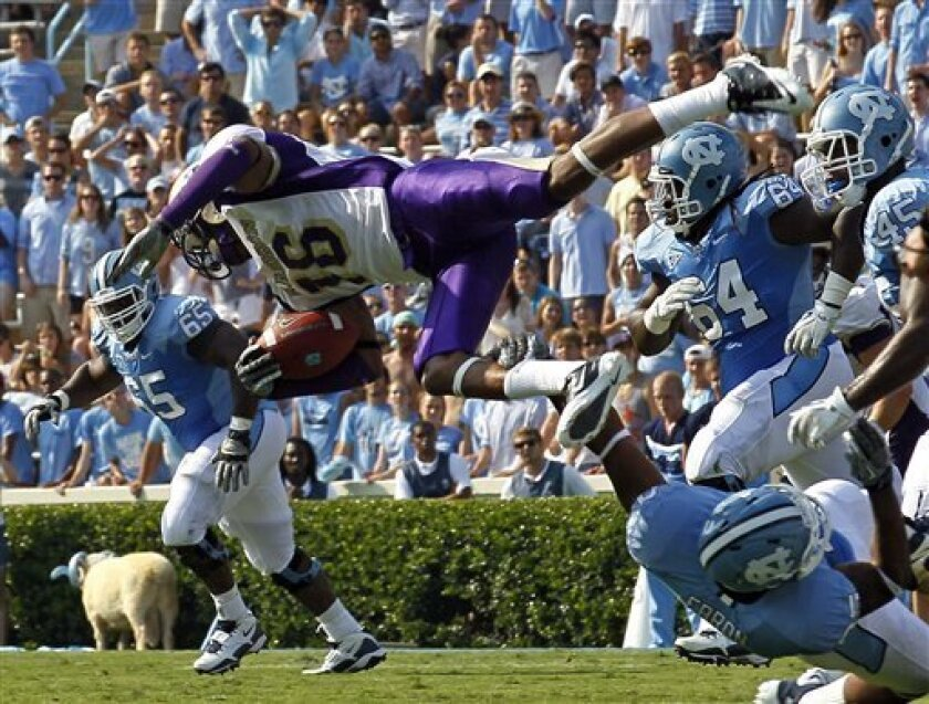 North Carolina's Eric Ebron, bottom right, upends James Madison's Dean Marlowe (16) during the first half of an NCAA college football game in Chapel Hill, N.C., Saturday, Sept. 3, 2011. North Carolina's Cam Holland (65) and Jonathan Cooper (64) assist. (AP Photo/Gerry Broome)