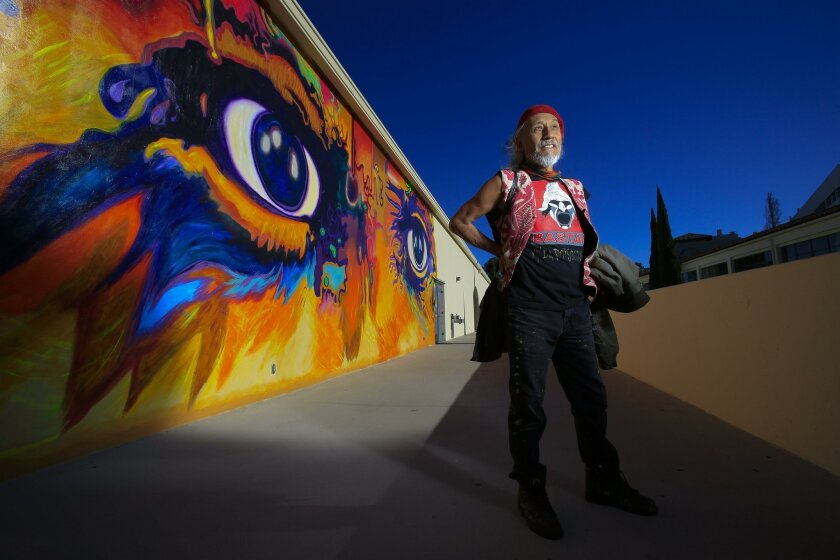 """Artist Mario Torero stands next to """"The Eyes of Picasso"""" painted on the fifth floor of the arts building at San Diego State University."""
