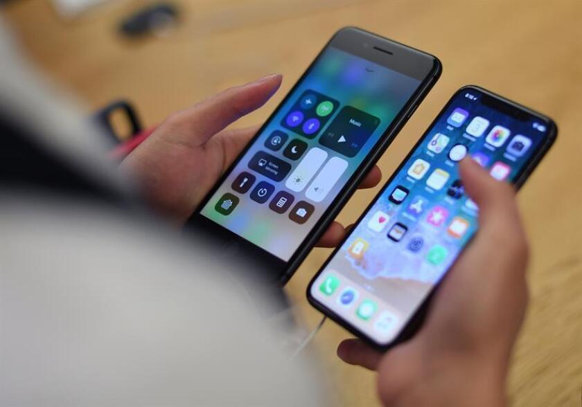 Un hombre compara el nuevo iPhone X con otro modelo iPhone durante el lanzamiento general al público del nuevo celular en una tienda Apple. EFE/Archivo