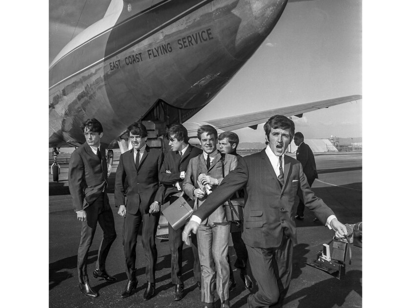 Nov. 15, 1964: Members of the Dave Clark Five are chilled by strong winds at LAX after landing. The group — from left, Mike Smith, Dave Clark, Dennis Payton, Lenny Davidson and Rick Huxley — deplaned at a remote airport location.