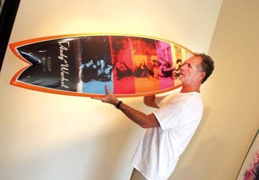 Tim Bessell displays his 5-foot, 7-inch fish-style surfboard, incorporating an image from one of Andy Warhol's final series of paintings, 'The Last Supper' (1986). Pat Sherman photos