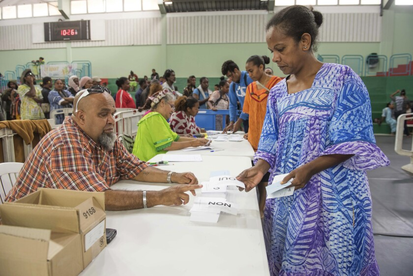 A woman participates in a referendum in New Caledonia, Sunday, Oct. 4, 2020, whether voters choose independence from France. Voters in New Caledonia, a French archipelago in the South Pacific, are deciding Sunday whether they want independence from France in a referendum that marks a milestone in a three-decade decolonization effort. (AP Photo/Mathurin Derel)