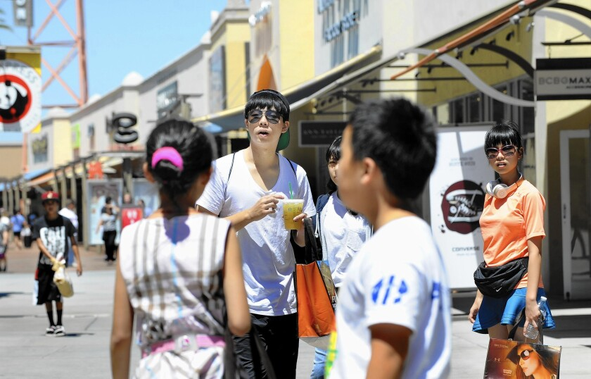 Tourism and entertainment, two major state industries that have thrived amid growing Chinese consumers, haven't seen signs of a slowdown. Above, Chinese tourists shop at the Citadel Outlets in City of Commerce.