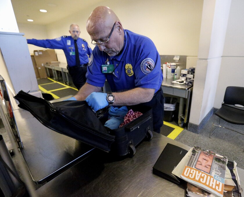 A TSA agent checks a bag at Midway International Airport in Chicago.