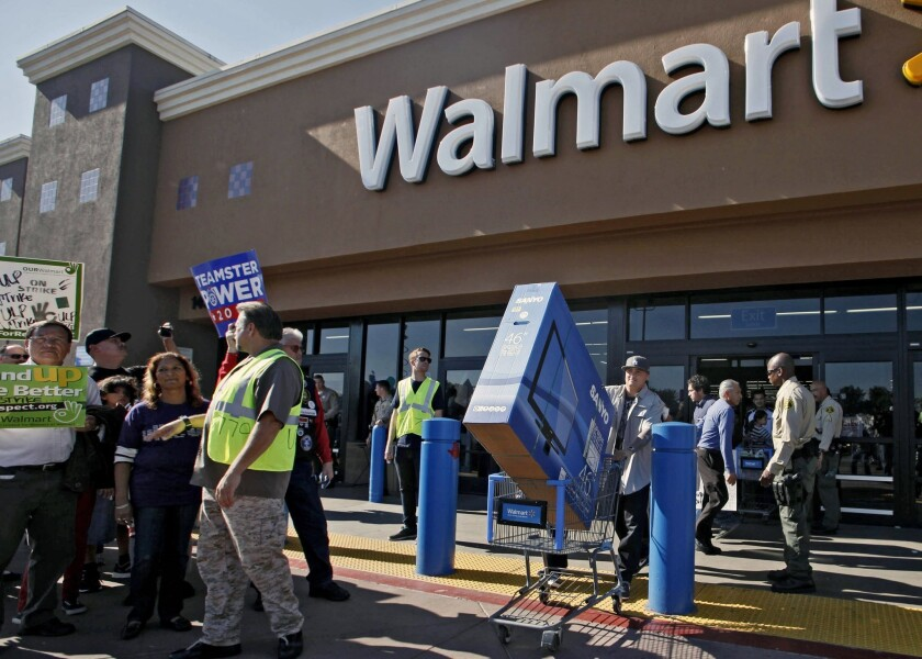 The National Labor Relations Board said earlier this month that union organizers can pay Black Friday protesters with a $50 gift card. Above, protesters at a Paramount, Calif., Walmart on last year's Black Friday.
