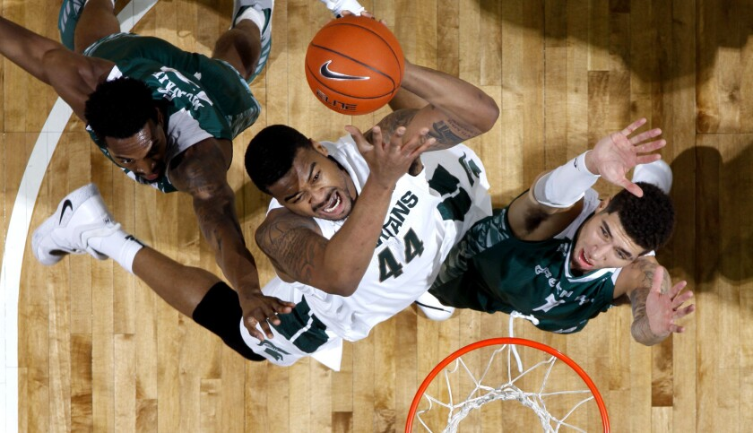 Michigan State's Nick Ward, center, shoots between Green Bay's Josh McNair, left, and Sandy Cohen II