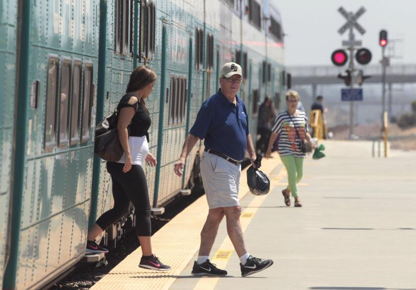 Passengers exit a northbound Coaster train at the Poinsettia station in Carlsbad.