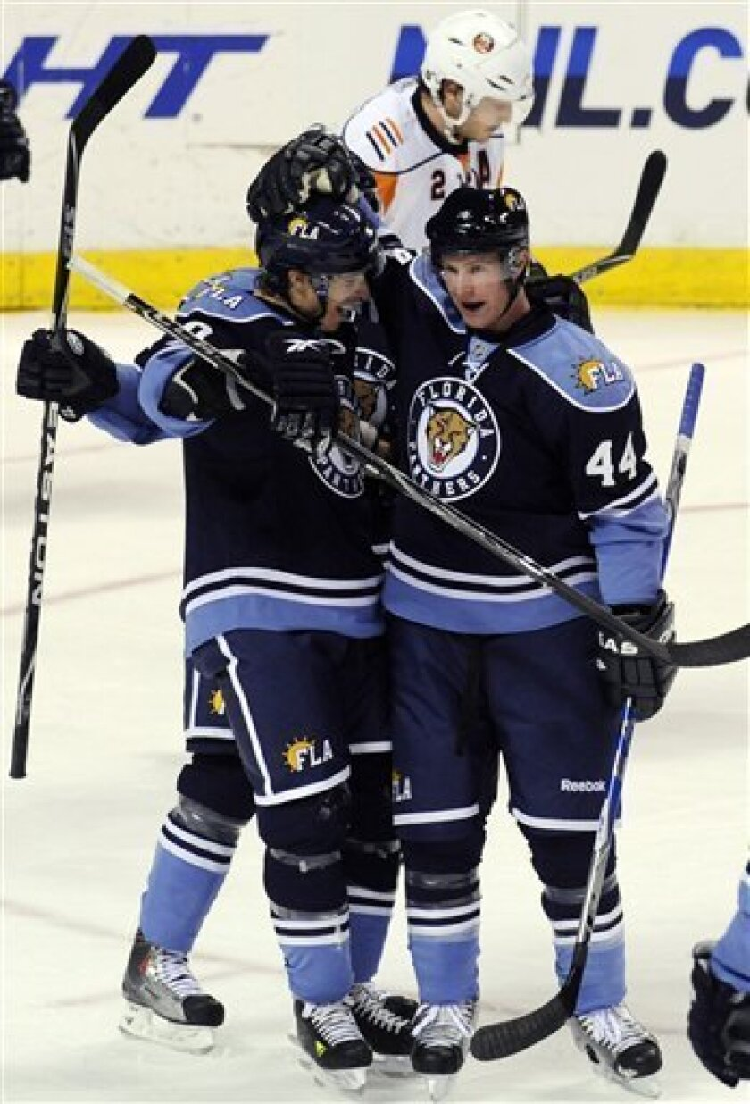 Florida Panthers' Jordan Leopold, right, celebrates his first-period goal against the New York Islanders with David Booth, left, during an NHL hockey game Sunday, Jan. 31, 2010, in Sunrise, Fla. Booth received an assist on the goal. (AP Photo/Rick Silva)