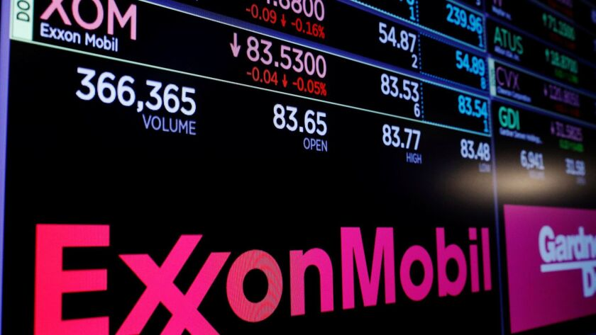 A logo of Exxon Mobil is displayed on a monitor above the floor of the New York Stock Exchange.