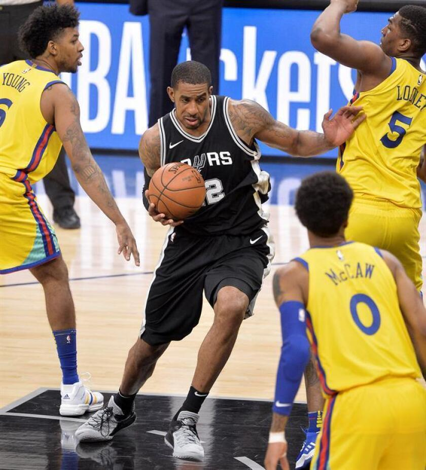 LaMarcus Aldridge (c) de San Antonio Spurs en acción ante Nick Young (i), Kevon Looney (5) y Patrick McCaw (0) de Golden State Warriors este lunes 19 de marzo de 2018, durante un partido de la NBA disputado en San Antonio, Texas (EE.UU.). EFE