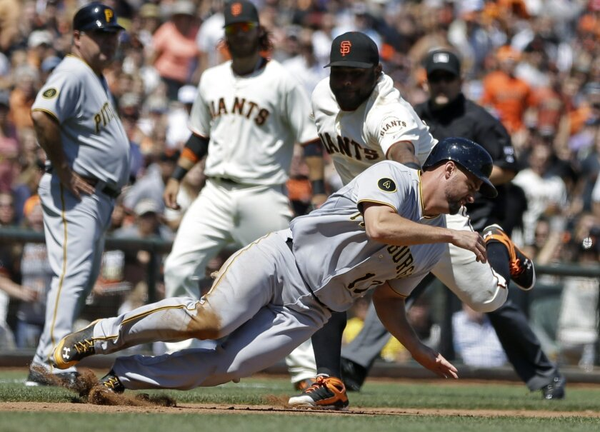 Pittsburgh Pirates' Gaby Sanchez, foreground, is tagged out while caught stealing by San Francisco Giants third baseman Pablo Sandoval in the sixth inning of a baseball game Wednesday, July 30, 2014, in San Francisco. (AP Photo/Ben Margot)