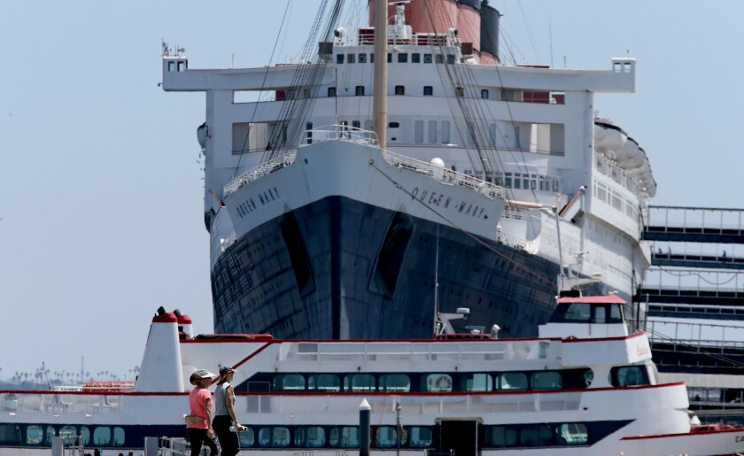 Strollers walk past the Queen Mary, a historic ocean liner that is permanently berthed in Long Beach.