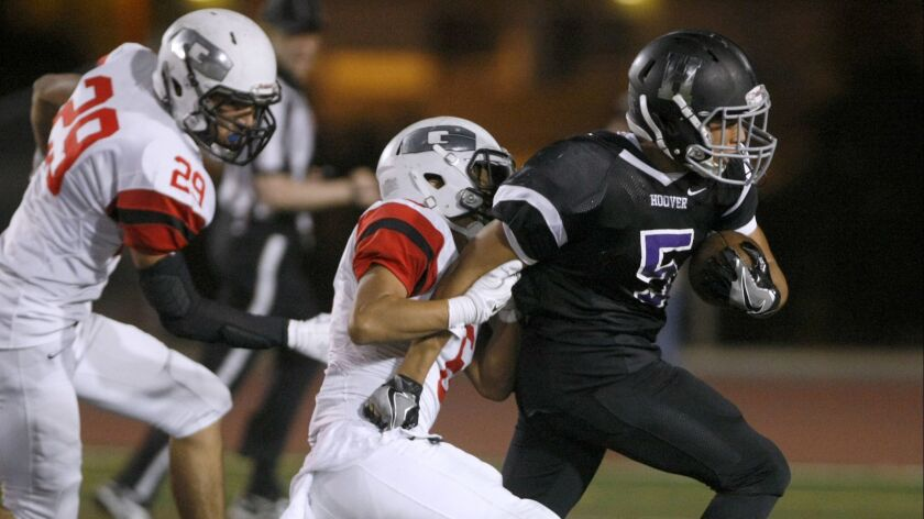 Hoover High School's #5 James Tumbucon is caught by Glendale High School's player #6 Anthony Luna in