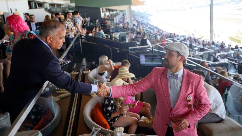 Santa Anita head Tim Ritvo shakes hands with customer Mike Duff on June 3.