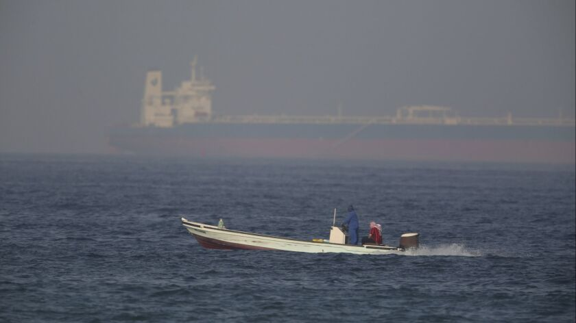 A fishing boat speeds past an oil tanker in the distance in Fujairah, United Arab Emirates, Saturday