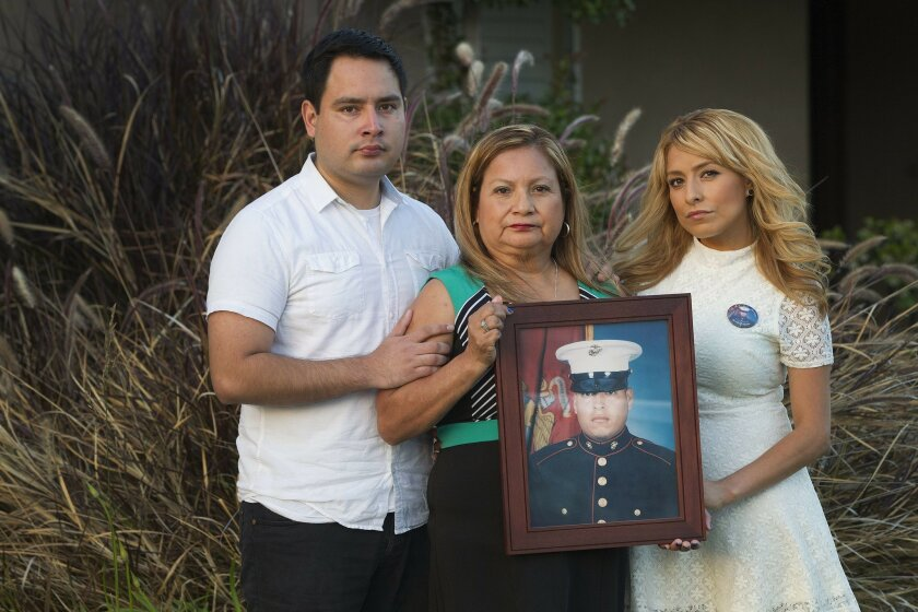 The late Rafael Peralta's family members gather with a framed photo of him in 2015. They are brother Rick, mother Rosa and sister Icela. / photo by Sean M. Haffey * U-T