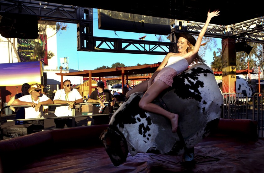 Ashlyn Ballou, 18, of Rancho Cucamonga, rides a mechanical bull at the Los Angeles County Fair in Pomona. The operators of the fair plan to improve security in the wake of mass shootings.