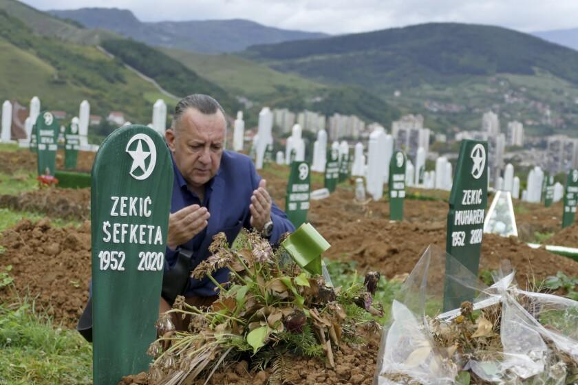 Tarik Svraka visits the graves of relatives who died of COVID-19 in Zenica, Bosnia.