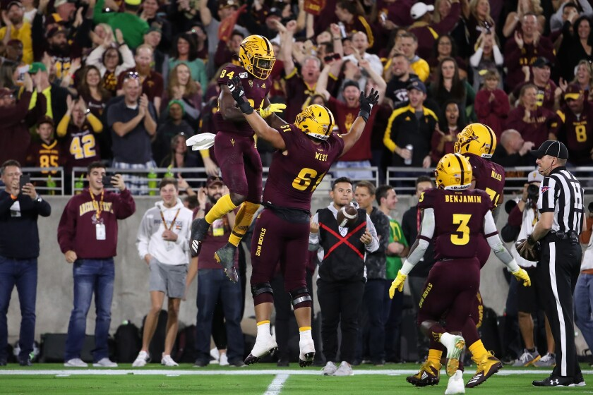 Arizona State's Frank Darby (84) celebrates with Dohnovan West after scoring a touchdown against Oregon on Nov. 23, 2019.