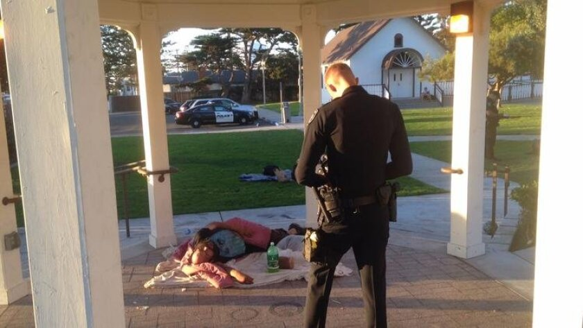 A Carlsbad police officer tickets a homeless man sleeping in Magee Park in 2019.
