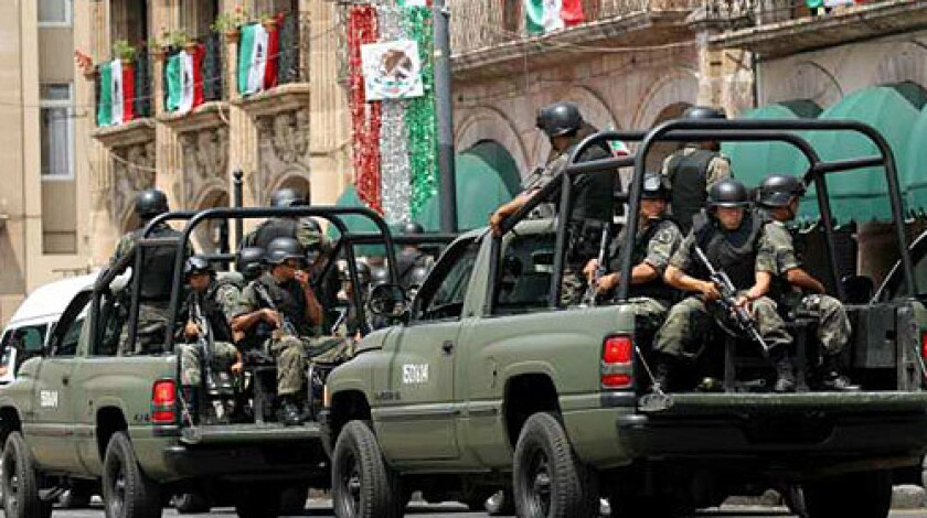 Soldiers ride on pickup trucks as they patrol the streets of Morelia on September 17 after deadly attacks on independence day celebrations sparked fears that civilians are now targets in the country's drug wars.