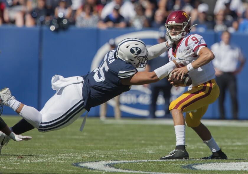 BYU's Lorenzo Fauatea tries to bring down USC quarterback Kedon Slovis during Saturday's game.