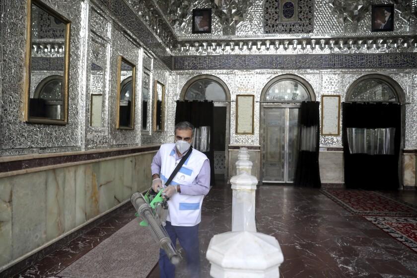 A man disinfects the shrine of the Shiite Saint Imam Abdulazim.