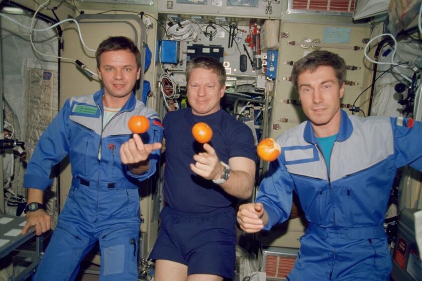 Expedition 1 crew members Yuri Gidzenko, from left, Bill Shepherd and Sergei Krikalev float with oranges on Dec. 4, 2000.