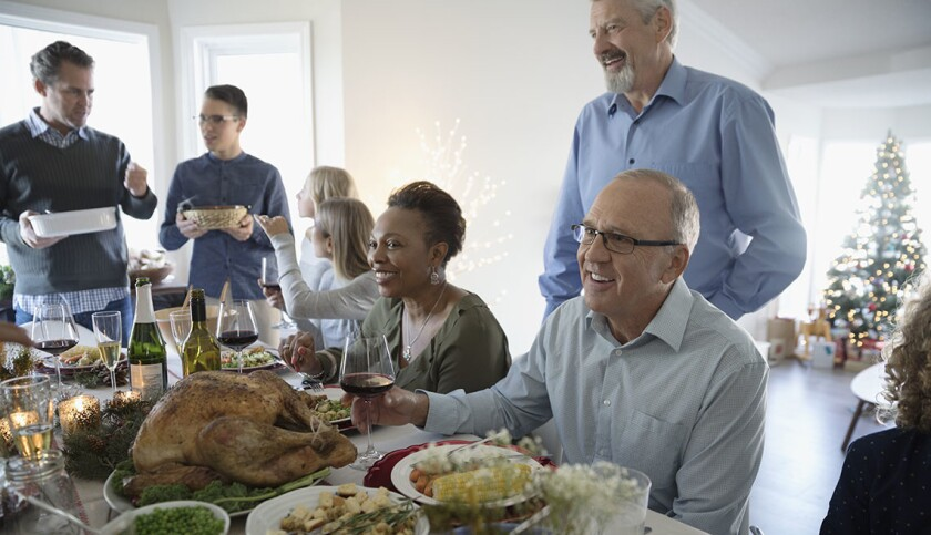 Family enjoying turkey Christmas dinner at table