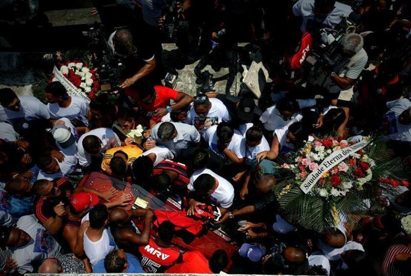 Amigos y familiares acompañan el féretro del joven arquero Christian Esmerio, una de las 10 jóvenes promesas del fútbol que perdió la vida en el incendio desatado el viernes en una de las sedes del club Flamengo, durante su sepelio este domingo en el cementerio de Iraja, en Río de Janeiro (Brasil). EFE