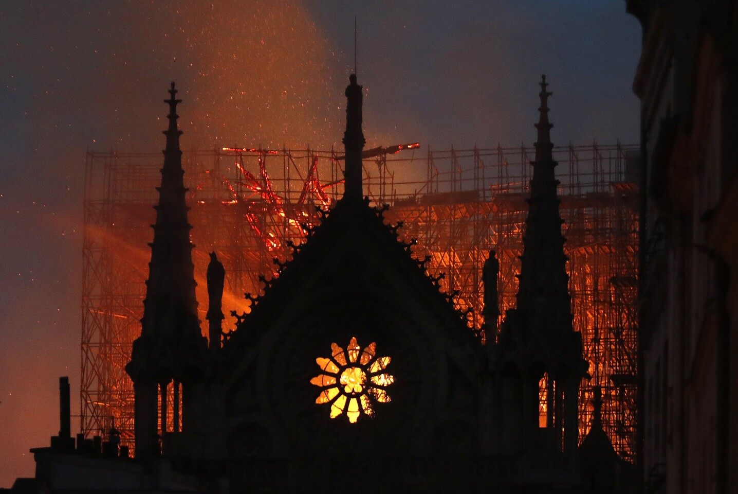 Flames and smoke rise from Notre Dame cathedral as it burns in Paris, Monday, April 15, 2019. Massive plumes of yellow brown smoke is filling the air above Notre Dame Cathedral and ash is falling on tourists and others around the island that marks the center of Paris.