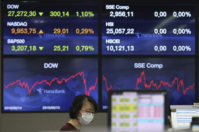 A currency trader watches monitors at the foreign exchange dealing room of the KEB Hana Bank headquarters in Seoul, South Korea, Wednesday, June 10, 2020. Shares were trading slightly higher in Asia on Wednesday after a weekslong rally on Wall Street hit the brakes. (AP Photo/Ahn Young-joon)