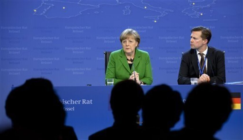German Chancellor Angela Merkel, center, listens to questions from journalists during a media conference at an EU summit in Brussels on Thursday, March 14, 2013. European Union heads of state and government meet for a two-day summit, beginning Thursday, to discuss the current financial crisis. (AP Photo/Virginia Mayo)