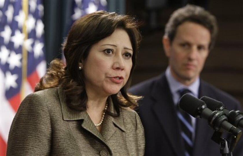 FILE - In this May 12, 2009 file photo, Labor Secretary Hilda Solis, left, accompanied by Treasury Secretary Timothy Geithner, speaks at the Treasury Department in Washington. (AP Photo/Alex Brandon, File)