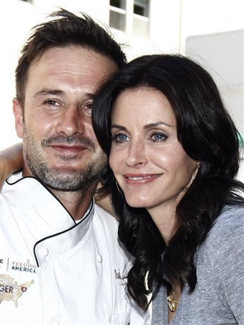 FILE - In this Aug. 31, 2009 file photo, David Arquette, left, and Courteney Cox Arquette pose together at the launch of The Cheesecake Factory's Drive Out Hunger Tour benefiting Feeding America in Culver City, Calif. (AP Photo/Matt Sayles, file)