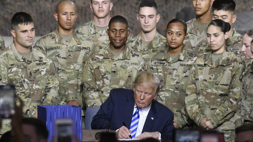 President Trump signs the John S. McCain National Defense Authorization Act in a ceremony at Ft. Drum, N.Y.